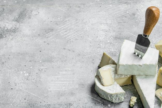 Сыр голубой и бри с ножами. на деревенской поверхности.