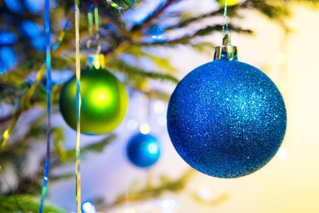 白黄色の背景にクリスマスツリーと青と緑のホリデーボール