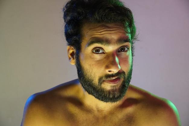 Синяя и зеленая молния на лице портрет мужчины в студии
