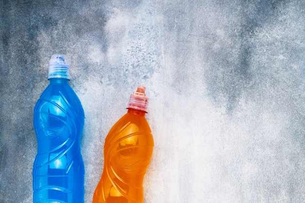 青とオレンジの等張エネルギードリンクは、グレーブルーの背景に。