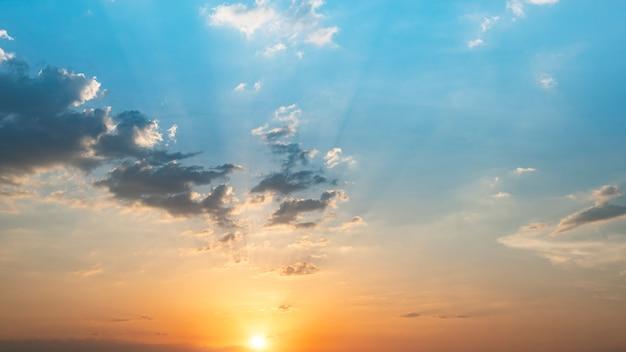 太陽光線と青とオレンジ色の夕焼け空。背景、早朝の空のシーンの自然の風景