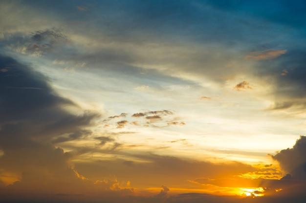 Голубое и оранжевое закатное небо с лучами солнца. природный ландшафт для фона