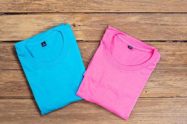 木の床の背景に置かれた青とピンクの綿のtシャツ。