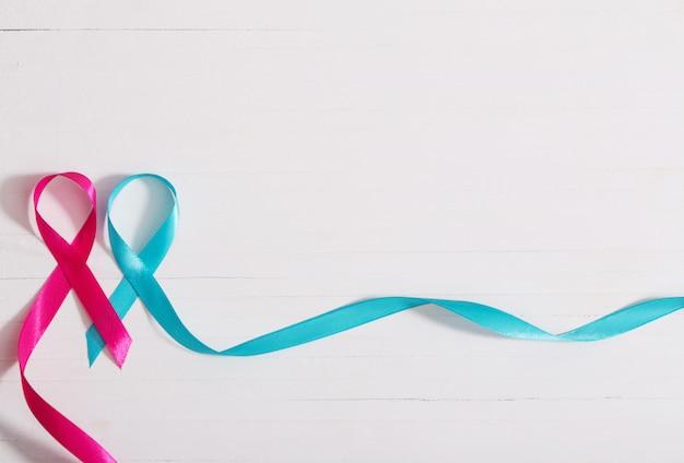 白い木製の壁に青とピンクのリボン