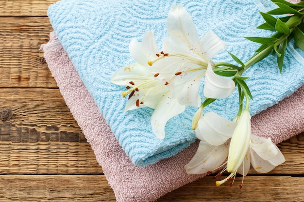 古い木の板に白いユリの花の花束と青とピンクの柔らかいテリータオル。上面図。
