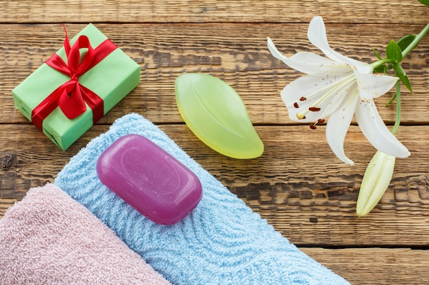 파란색과 분홍색의 부드러운 테리 수건, 선물 상자, 비누, 흰색 백합 꽃이 오래된 나무 판자에 있습니다. 평면도.