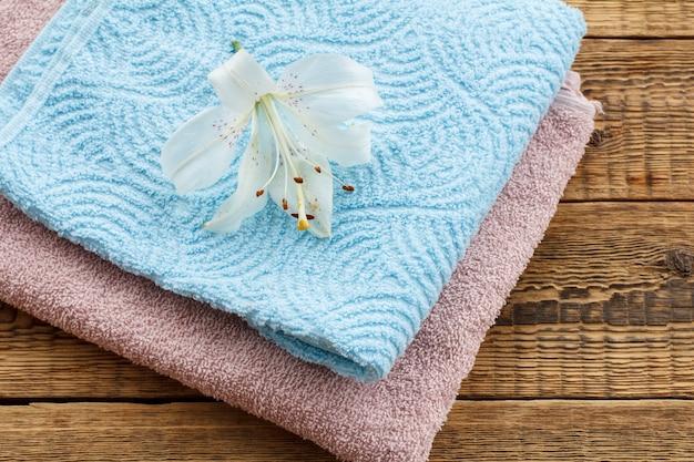 古い木の板に白いユリの花と青とピンクの柔らかいテリータオル。上面図。