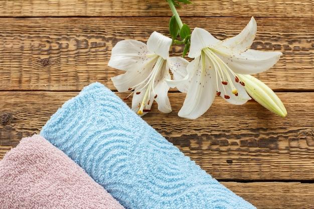 古い木の板に白いユリの花が付いた青とピンクの柔らかいテリータオル。上面図。