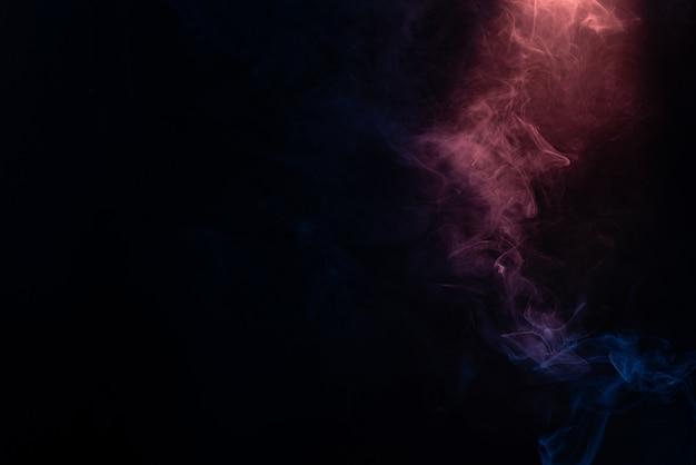 검은 색 표면에 파란색과 분홍색 증기. 공간을 복사하십시오.