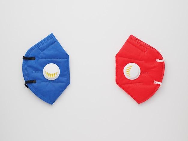 白い卓上に青と赤の色のkn95マスク。