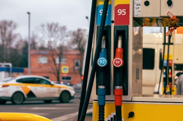 Синие и красные форсунки бензонасоса на заправочной станции. 92 и 95 окатановое число.