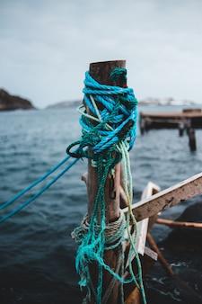 Синяя и красная веревка на коричневом деревянном столбе