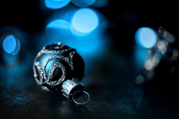 Синий и серебряный елочный шар на темной гирлянде с подсветкой