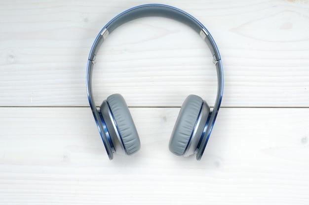 白い木の上で音楽を聴くための青と銀のモダンなヘッドフォン