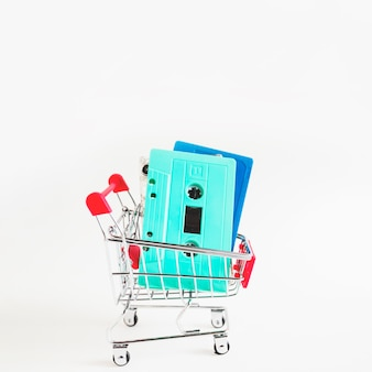 Blue and turquoise cassette tapes in shopping cart isolated over white background