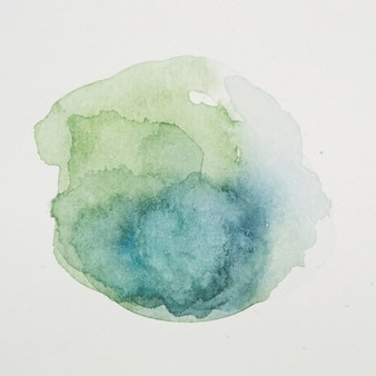Blue and verdant paints in form of circle on white paper