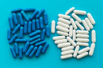 Blue and white candy capsules on cyan backdrop