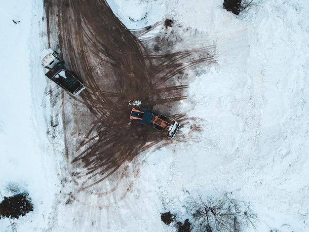 雪に覆われた地面に青と白の車