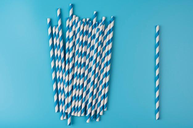 明るい背景の飲料用の青と白のストロー。 1本のストローと多くのストローのコンセプト。生態学的変動
