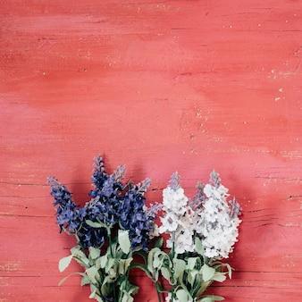淡いピンクの木製の背景に青と白のラベンダー