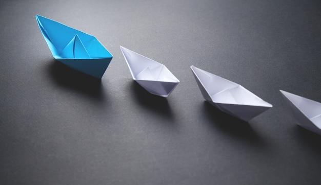 파란색과 흰색 종이 보트. 리더십 개념