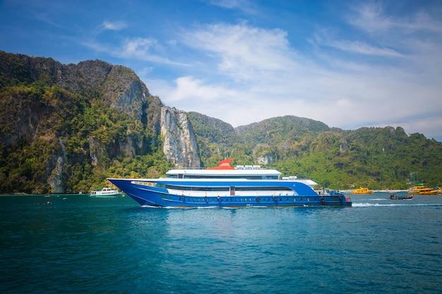 파란색과 흰색 여객선은 다른 배 산과 함께 목적지 항구로 항해합니다.