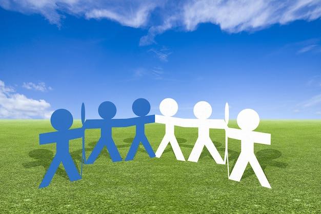 Бумага синих и белых людей, взявшись за руки, стоя на лугу. концепция всемирного дня народонаселения