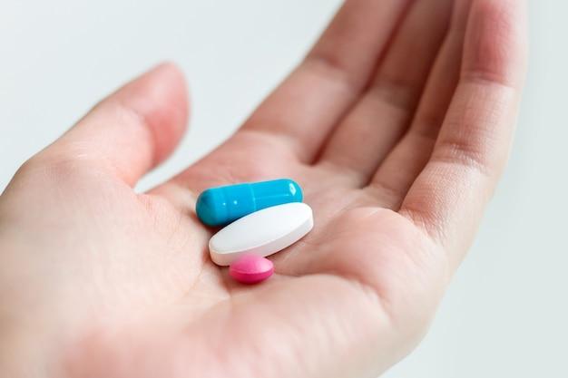白い背景の上の女性の手のひらに青と白の錠剤カプセル。女性の手で抗うつ薬。