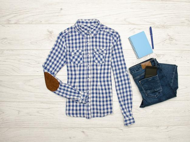 Сине-белая рубашка в клетку, джинсы, мобильный телефон, синий блокнот с ручкой. деревянный фон. модная концепция, вид сверху