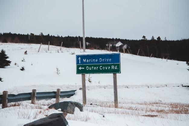 雪に覆われた地面に青と白の道路標識