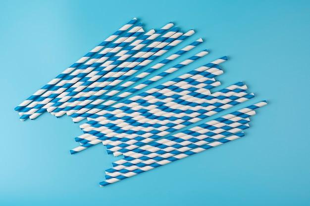 青と白のストロー青の背景にストローを飲む縞模様の紙上面図環境にやさしい