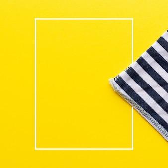 Сине-белый полосатый треугольник из ткани на ярко-желтом фоне с белой прямоугольной рамкой посередине. вид сверху с копией пространства. шаблон летней концепции для рекламы, продаж, акций