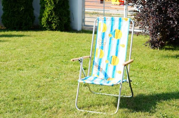 Сине-белый полосатый шезлонг на зеленой траве