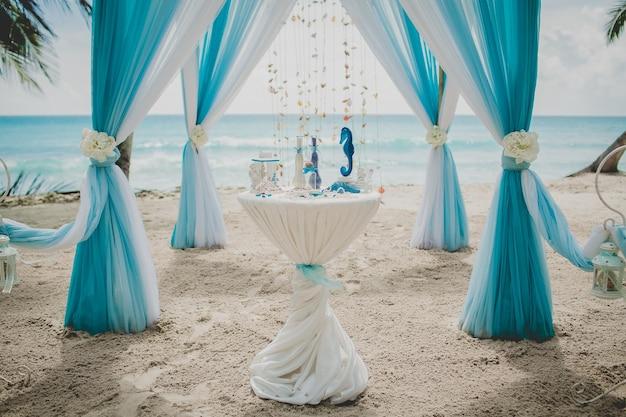 배경에 바다와 야자수로 둘러싸인 해변에서 파란색과 흰색 결혼식 통로
