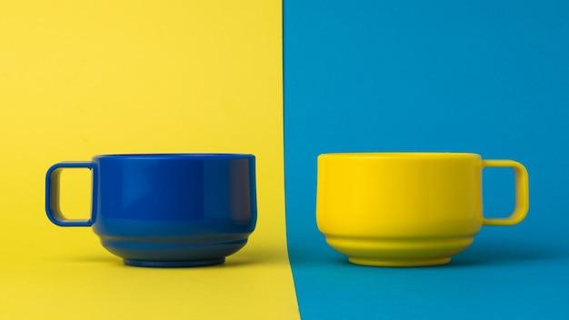 노란색과 파란색 표면에 파란색과 노란색 커피 또는 차 컵