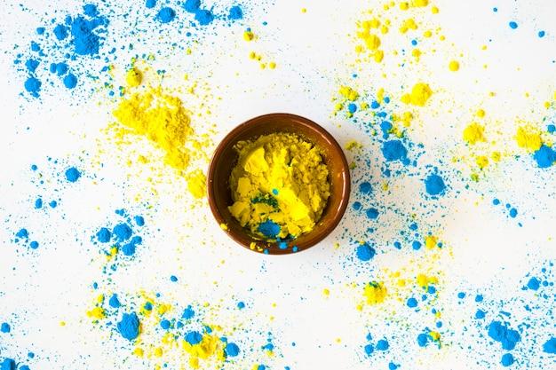 Синий и желтый цвет порошка вокруг чаши на белом фоне