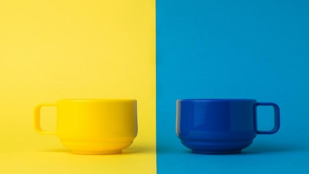 Синие и желтые чашки на синем и желтом фоне. цветовой тренд.