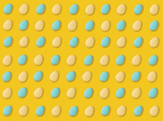 Голубое и желтое печенье пасхального яйца на желтом фоне.