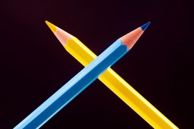 Синие и желтые карандаши для рисования. образование и творчество. досуг и искусство