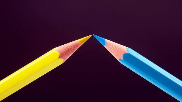 어두운 배경에 그리기위한 파란색과 노란색 연필. 교육과 창의성. 여가와 예술
