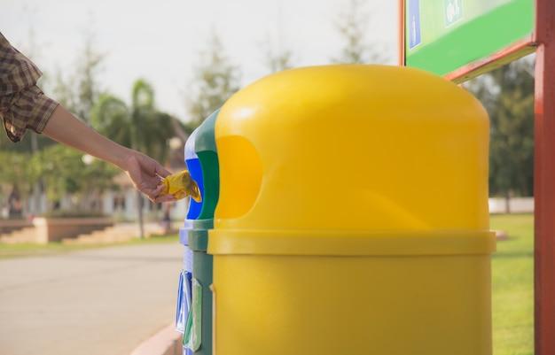 여름에 공원에서 파란색과 노란색 플라스틱 휴지통. 컬러 쓰레기통.