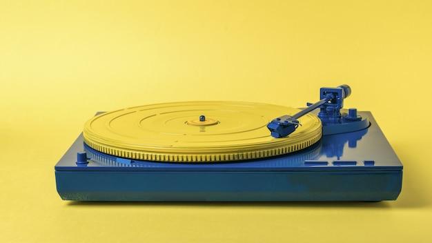 黄色の背景に青と黄色のビンテージビニールレコードプレーヤー。レトロな音楽機器。