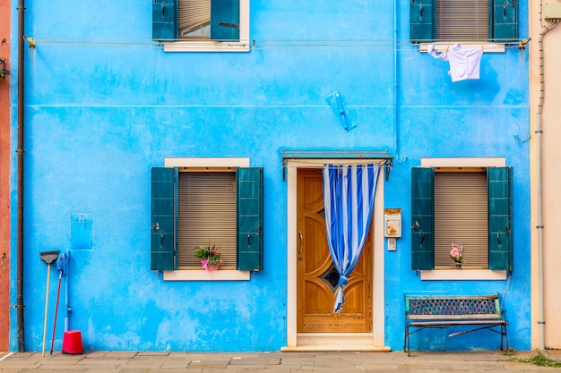 Blue aqua colored house with flowers and bench. colorful houses in burano island near venice, italy.