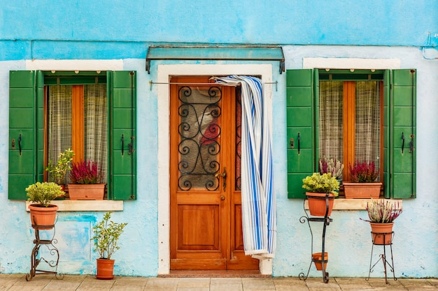 Blue aqua colored house with flowers and plants. colorful houses in burano island near venice, italy. venice postcard.