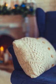 ニットベージュの枕、モダンなインテリアと青いアームチェア