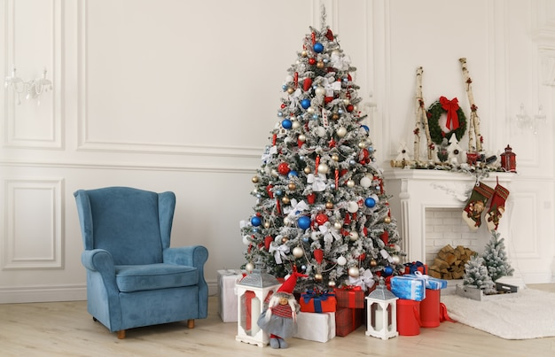 Blue armchair and gift boxes under decorated christmas tree beside decorated fireplace