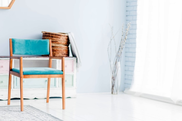 A blue armchair stands in front of a window with white curtains. horizontal photo