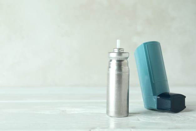 Синий ингалятор астмы на белом деревянном столе