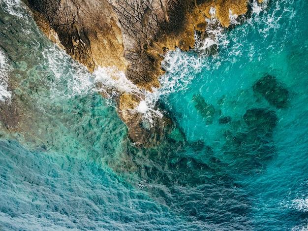 푸른 푸른 바다 물 하얀 거품 파도가 바위 해안 공중 평면도를 치는