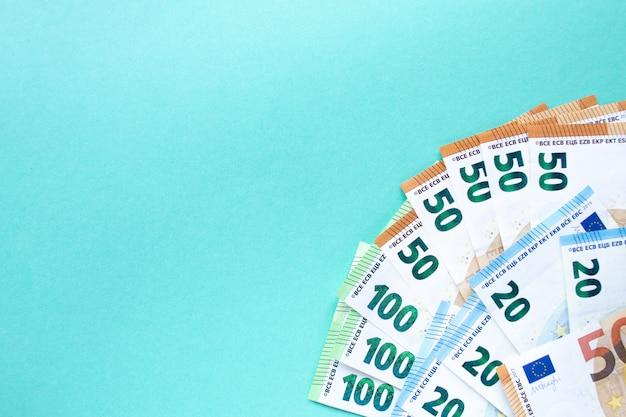 Синий фон банкноты номиналом 100, 50 и 20 евро в левом нижнем углу. понятие денег и финансов. с местом для текста.